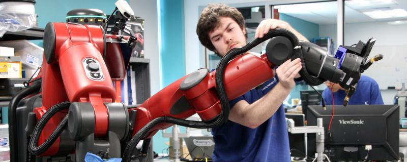 Duke Robotics lab member adjusts arms on the robo-nurse, TRINA
