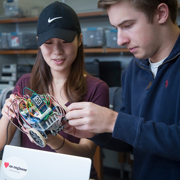 Duke students hold a robotic vehicle
