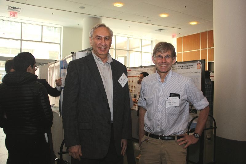 Michael Rubinstein and Stefan Zauscher peruse research posters at the 2019 Triangle Soft Matter Workshop